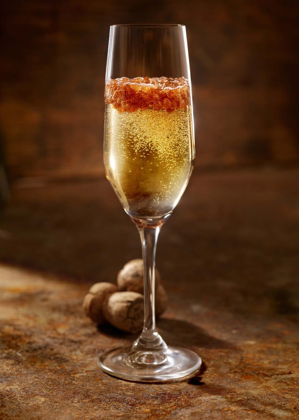 Calgary Beverage Photographer. A Glass of bubbly full of berries on rustic backdrop.
