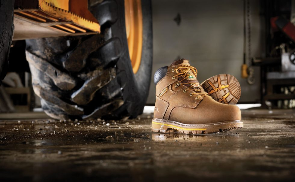 Calgary Commercial Photography. Work boots on display next to construction vehicle in the garage.