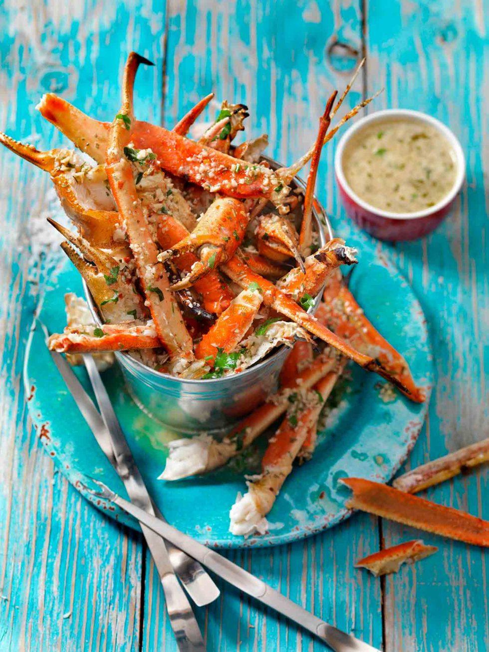 Calgary Food Photography. Seasoned display of crab legs on light blue backdrop.