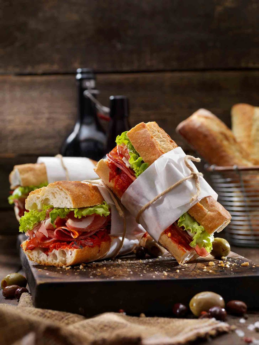 Calgary Food Photography. Fresh wrapped and tied deli sandwiches on rustic backdrop.