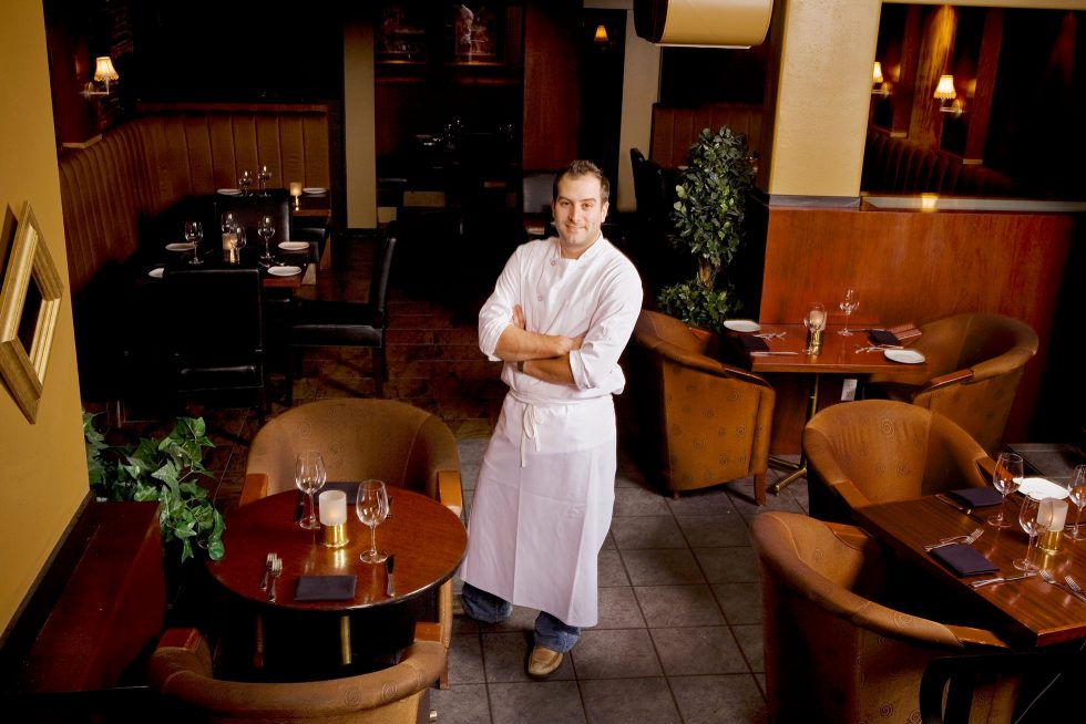 Calgary People Photographer. Chef standing in dining area with arms crossed.