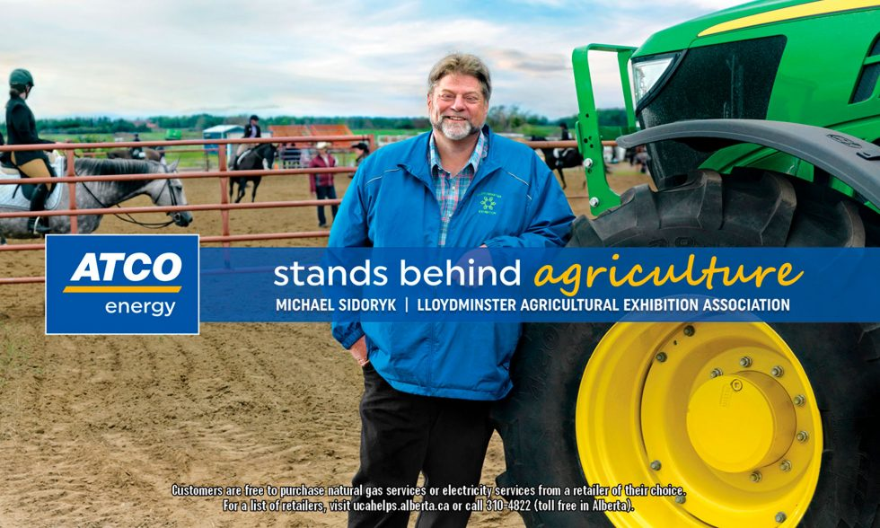 Calgary People Photographer. Man leaning against tractor tire. Lloydminster agricultural exhibition association.