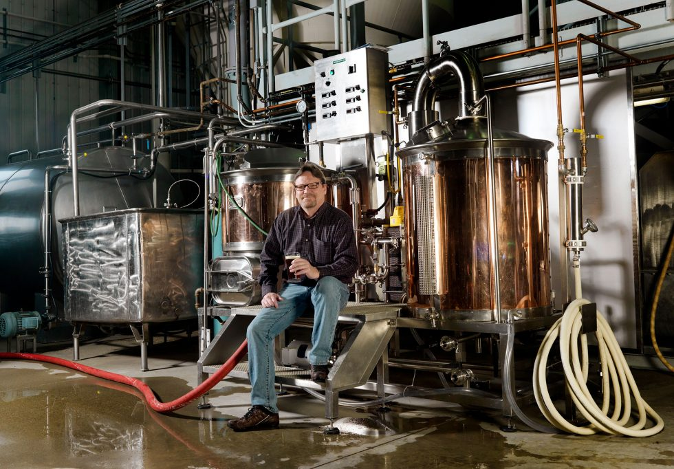 Calgary People Photographer. Man sitting in brewery with beer in hand.
